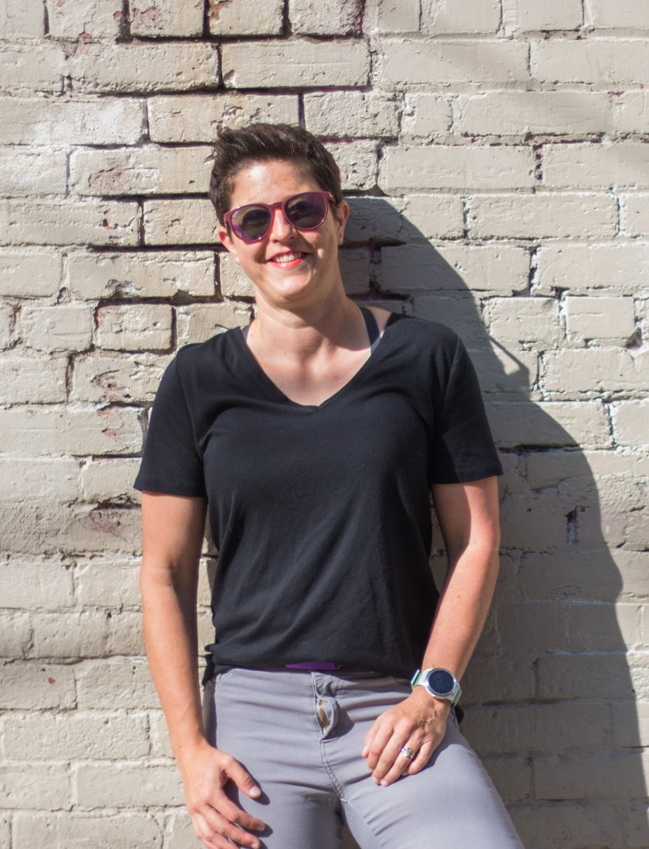 Casey leaning against a white brick wall. Wearing a black tee and sunglasses